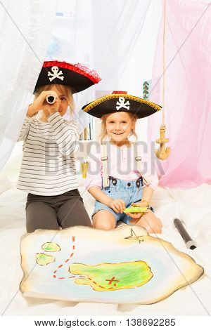 Two cute girls in costumes of pirates looking through a toy spyglass
