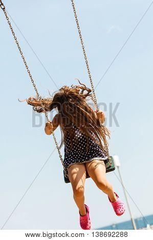 Girl Swinging On Swing-set.
