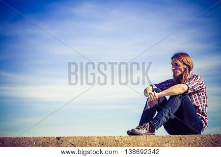 Man long hair wearing plaid shirt relaxing outdoor sitting on concrete wall at sunny windy day against blue sky