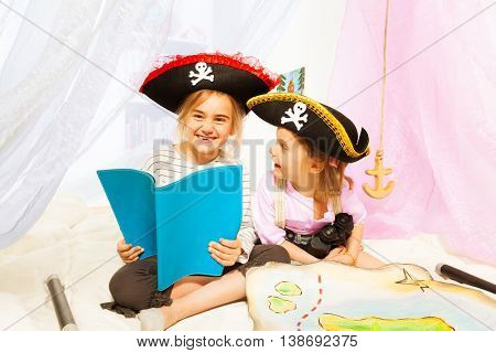 Two happy girls in pirate's costumes, reading blanked book about pirate's treasures