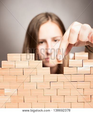 young woman building a wall on a grey background