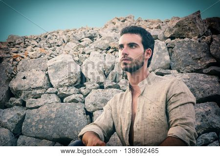 Ruggedly Handsome Man in front of big rocks and stones, could be an archaelogist