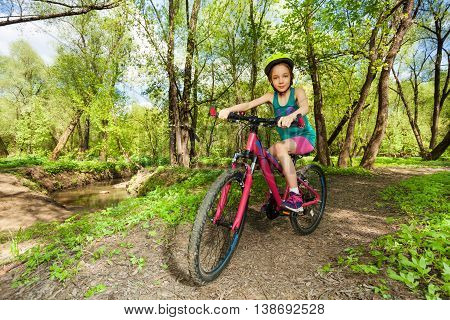 Young girl in bicycle helmet cycling mountain bike on the forest trail in the spring time