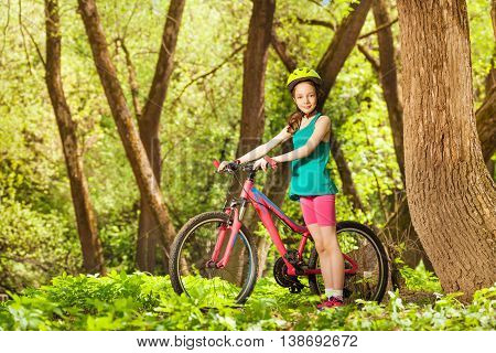 Picture of young girl in bicycle helmet, standing with her mountain bike in sunny spring park