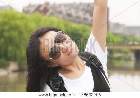 A triumphant Chinese woman wearing sunglasses raising her arm outside with a blurred background.