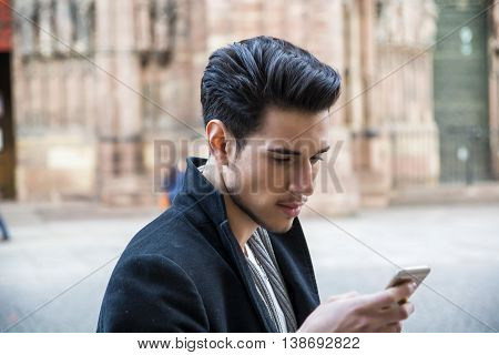 Young dark haired man standing in European city, using smartphone to send text message or surfing the internet