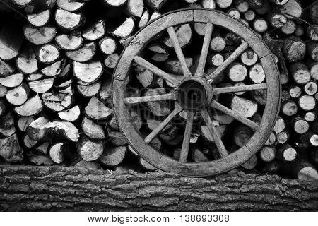 Pile of chopped wood with a wooden wheel prepared for the winter