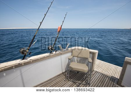 View of tropical ocean from back of a luxury sports motor boat with fishing rods