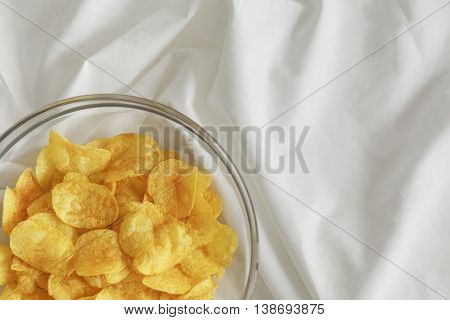 chips poured in a transparent bowl on a white cloth