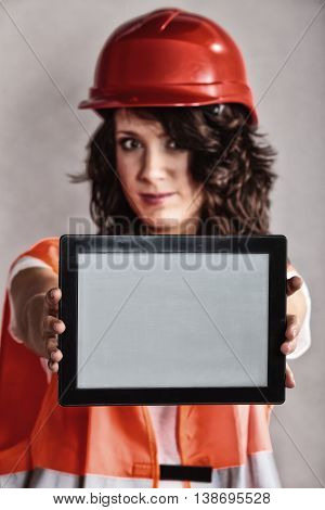 Sex equality and feminism. Sexy girl worker in safety helmet and orange vest showing copy space on tablet touchpad.