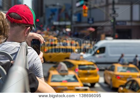 NEW YORK, UNITED STATES - JUN 22, 2016: Tourist photographs the streets of New York taxis filled with tourist bus