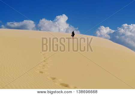Man walking bare feet on a sand dune