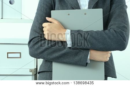 Portrait of business woman standing with folder, cool tone