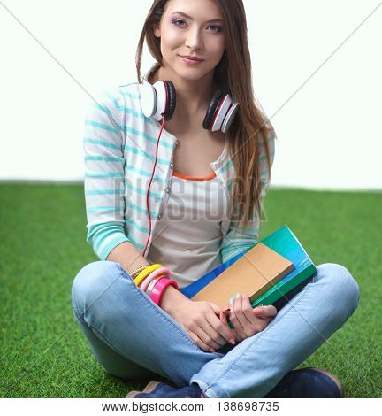 Woman reading book sits on the green grass