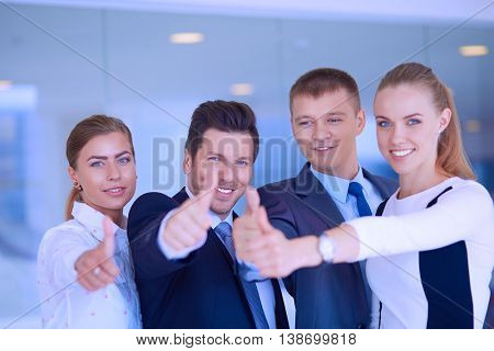Happy business team showing thumbs up in office