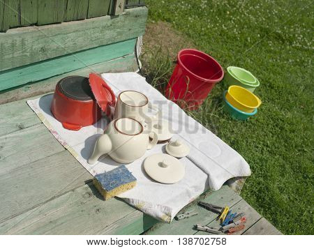 A bunch of upside down cups, casserole drying  on a wooden porch, a lawn with colorful plastic baskets in the background