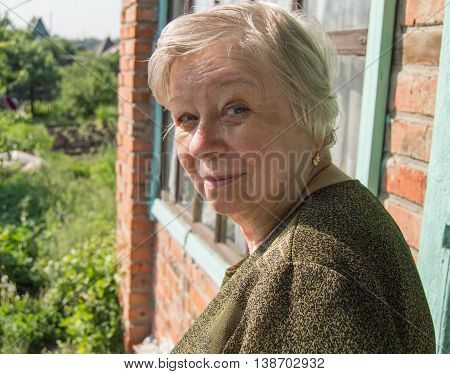 Happy old woman near his home in the garden.