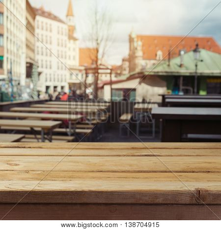 Empty wooden deck table over beer garden restaurant background for product montage display. Octoberfest background.