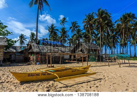 A yellow outrigger boat on a beach near a village of thatched huts in the Philippines