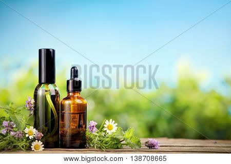 Mint essential oil in small brown bottles and fresh mint
