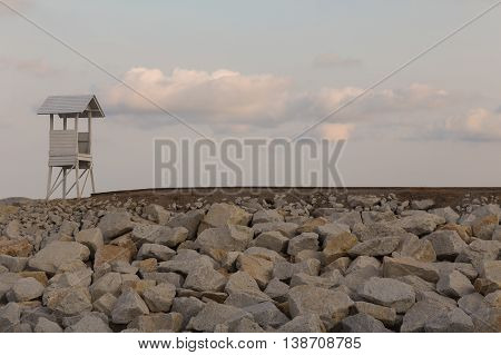 Lifeguard over rocky walkway with natural sky background