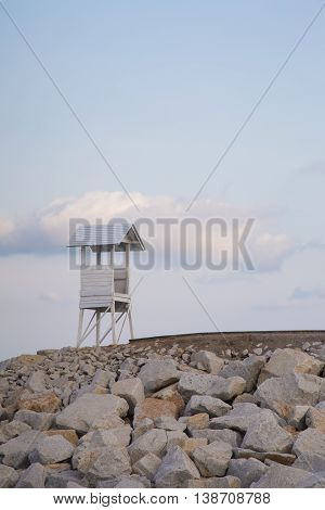 Lifeguard stand over rock walkway with natural sky background