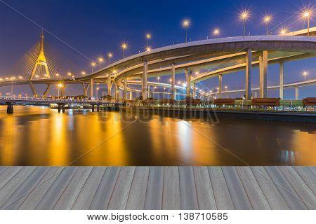 Opening wooden floor, Twilight waterfront over highway interchange connect suspension bridge background