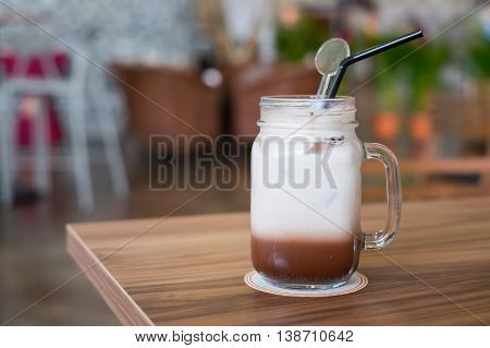 Iced chocolate with milk in retro glass jar (Mason Jar) on wooden table in cafe.