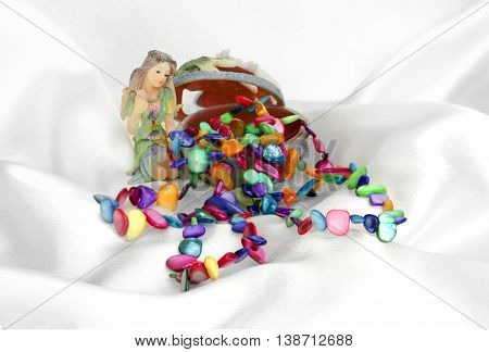 bright beads in a box made up fairy doll necklace on the silk background