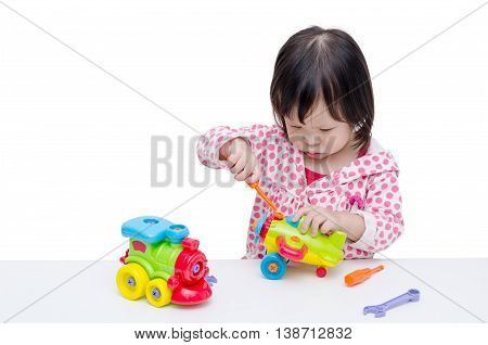 Little Asian girl playing with plane and train toy