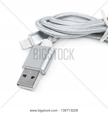 Folded USB lightning silver metal cable isolated over the white background, close-up crop fragment