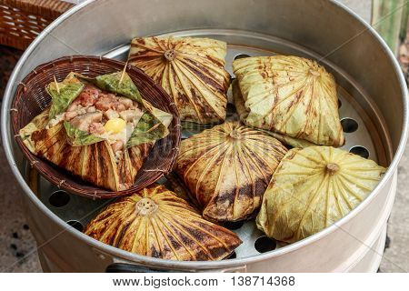 Sticky rice wrapped in lotus leaf or Zongzi is traditional Chinese food is made with sticky rice and pork, sausage, mushrooms, nuts, ginkgo wrapped in to lotus leaf and in steaming pot. Chinese style steamed.