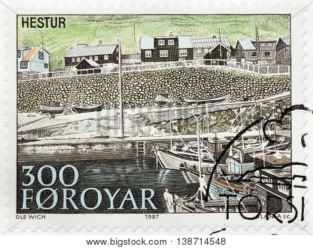 LUGA RUSSIA - JUNE 25 2016: A stamp printed by FAROE ISLANDS shows view of Hestur - an island in the central Faroe Islands. The island has one settlement a village also named Hestur circa 1987.