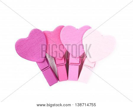 Pile of multiple tiny heart shaped colored wooden peg pins, composition isolated over the white background