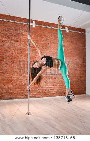 Young sexy pole dance woman doing acrobatic tricks with pylon.
