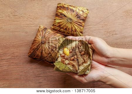 Freshly cooked sticky rice wrapped in lotus leaf holding and peeling on woman hands with wooden background. Sticky rice wrapped in lotus leaf or Zongzi is traditional Chinese food.