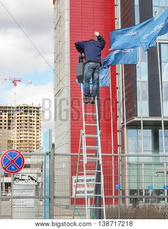 St. Petersburg, Russia - 7 April, Job electrician on a ladder with a lantern, 7 April, 2016. Urban workers profession and people at work.