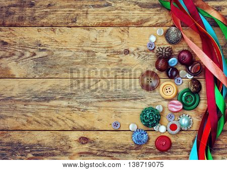 ancient variety buttons and multicolored ribbons lie on wooden table