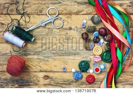 scissors thread variety buttons multicolored ribbons lying on old wooden table