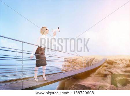 Businesswoman standing on bridge leading to cliff using megaphone on sea and sky with sunlight background