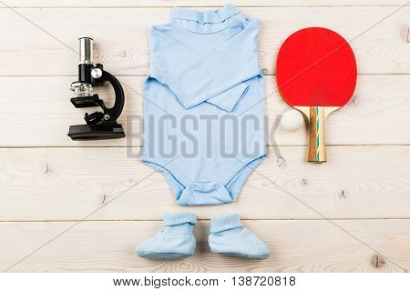 Future occupation concept. Top view of blue baby boy outfit surrounded with microscope and table tennis equipment on light wooden surface
