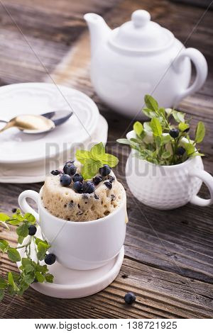 Healthy breakfast. Fresh homemade mug cake with forest blueberries in a white ceramic bowl with a sprig of ripe berries on the gray wooden background. selective focus