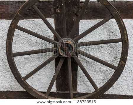 The old wheel on wall of farmhouse