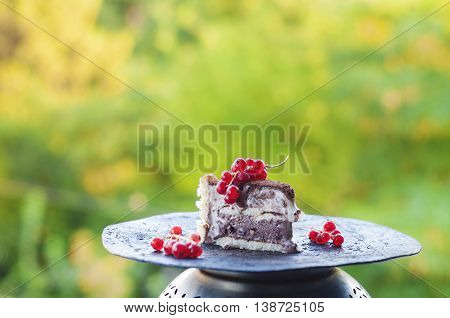 Slice of ice cream tiramisu cake with cranberries on grungy metal plate.