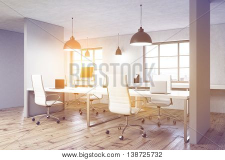 Coworking office interior with wooden floor concrete walls ceiling lamps computer monitors on desks windows with city view and sunlight. Toned image 3D Rendering
