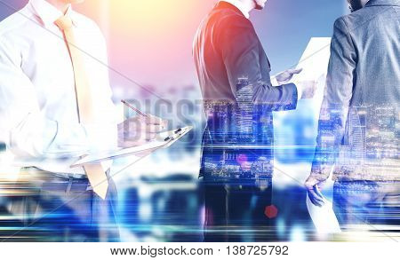Businessmen working on illuminated night city background with abstract sunlight. Teamwork and partnership concept. Double exposure