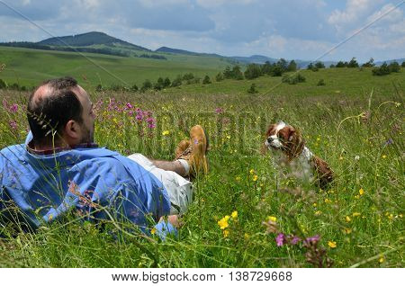 Man is resting on a meadow with his dog Cavalier King Charles Spaniel