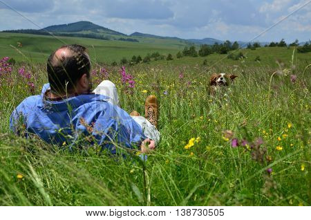 Man lying on a spring meadow and looking after his dog