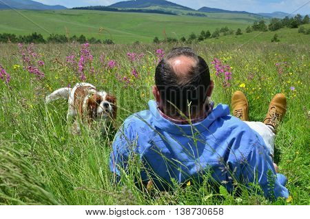 Man resting on green grass with wildflowers and looking at his dog