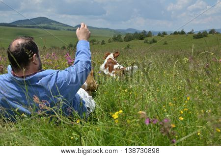 Man is throwing a toy to his dog on mountain meadow